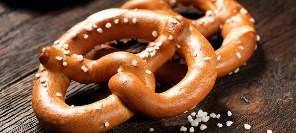 Fresh pretzels with sea salt close-up on  dark board background